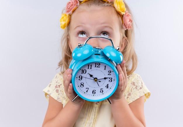 Una bambina adorabile che porta la camicia gialla nella fascia floreale che mostra la sveglia blu mentre osserva in su su una parete bianca