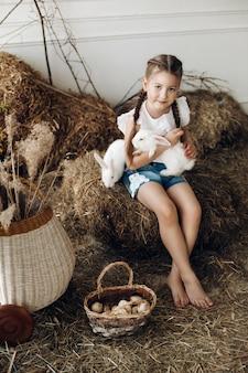 Прекрасная маленькая девочка с косами держит двух очаровательных кроликов.