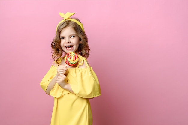 Lovely little girl with candy on pink