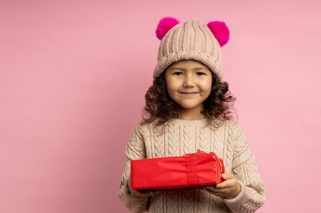 Милая маленькая девочка с вьющимися волосами, одетая в теплый свитер, шляпу с двумя ярко-розовыми пушистыми помпонами, держит красную подарочную коробку и улыбается изолированно