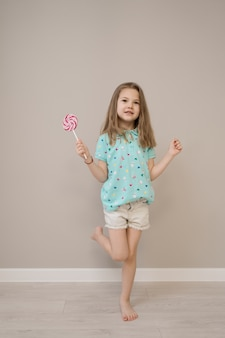 Lovely little girl with lollypops on beige background