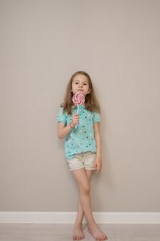 베이지 색 배경에 사탕과 사랑스러운 작은 소녀