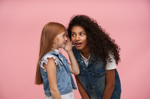 Lovely little girl with long foxy hair keeping palm near her mouth and whispering some news to young dark skinned curly brunette female, isolated on pink