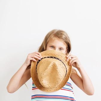 Милая маленькая девочка в соломенной шляпе