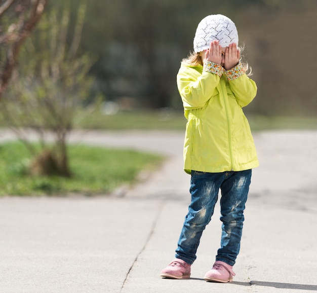 Lovely little girl in yellow coat hiding face with hands