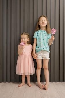 회색 배경에 사탕과 사랑스러운 작은 소녀