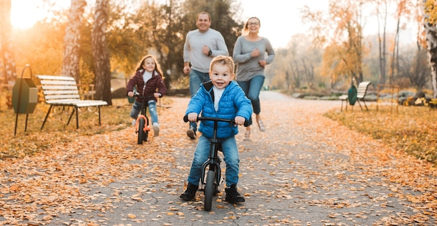 Милый маленький ребенок убегает от него, пока ее родители и сестра пытаются поймать его на улице в парке.