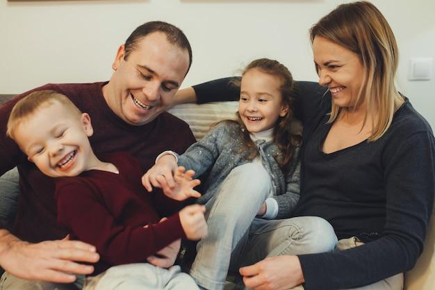 自宅のソファで両親と遊んでいる間、笑いを楽しんでいる素敵な妹と弟。子供と遊ぶ母と父。