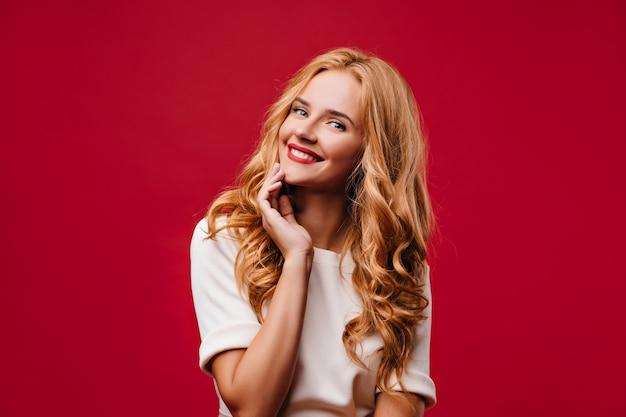 写真撮影中に微笑んでいる素敵な長髪の女の子。赤い壁に立っている陽気な笑いの女性。