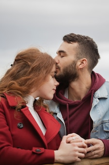 Lovely man kissing girlfriend's forehead