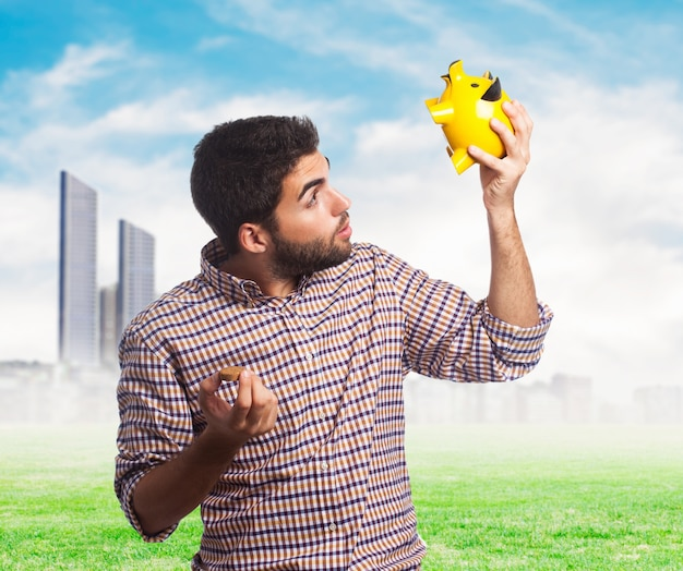 Lovely man looking in yellow piggy bank
