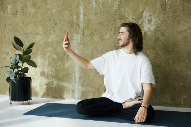 Lovely man in yoga pose on mat using phone,remote practice of yoga or meditation online through phone, copy space