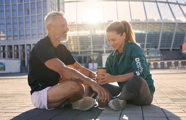 Прекрасная зрелая пара в спортивной одежде общается друг с другом, попивая расслабляющий кофе