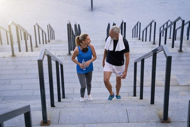 Прекрасная зрелая пара мужчина и женщина в спортивной одежде улыбаются друг другу, поднимаясь по лестнице после