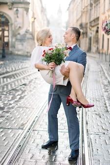 오래 된 도시에서 야외에서 웃 고 서로 찾고 사랑스러운 성숙한 부부