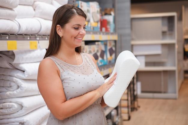 Милая зрелая домохозяйка рассматривает ортопедическую подушку в продаже в магазине товаров для дома