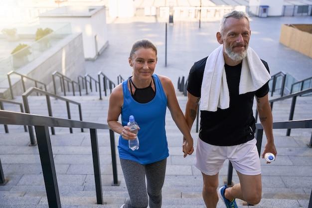 Прекрасная пара средних лет из спортивного мужчины и женщины, выглядящих счастливыми, держась за руки, поднимаясь вверх