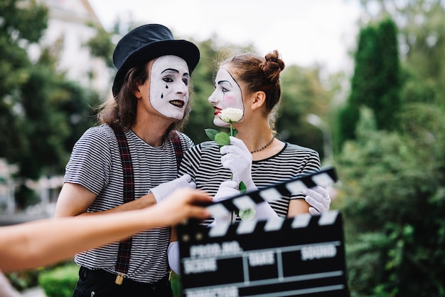 Lovely mime couple with flower standing in park