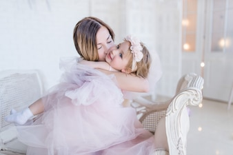 Lovely mom and daughter hug each other tender sitting on white chair