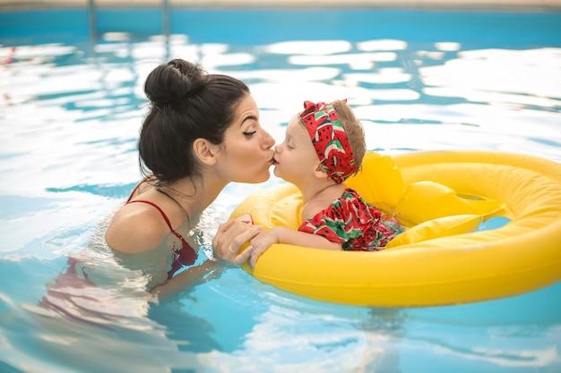 Милая мама целует своего ребенка во время плавания в бассейне
