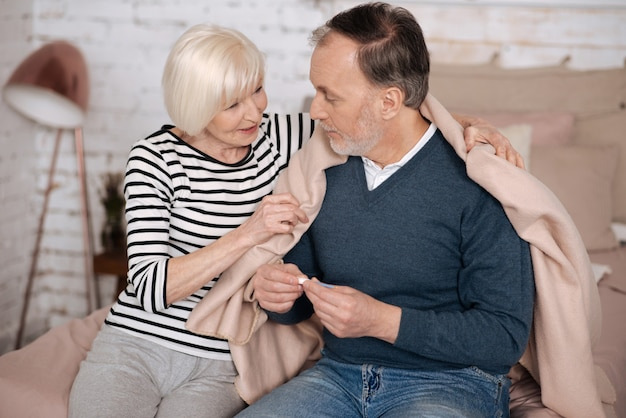 Прекрасный момент. довольно улыбается старшая дама накрывает своего больного мужа теплым одеялом, сидя на кровати.