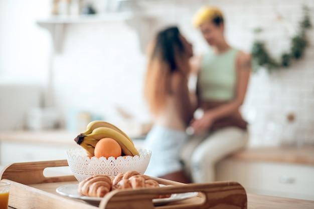 素敵な朝。トレイに新鮮な果物とおいしいクロワッサン、朝のキッチンで遠くでおしゃべりする恋のガールフレンド