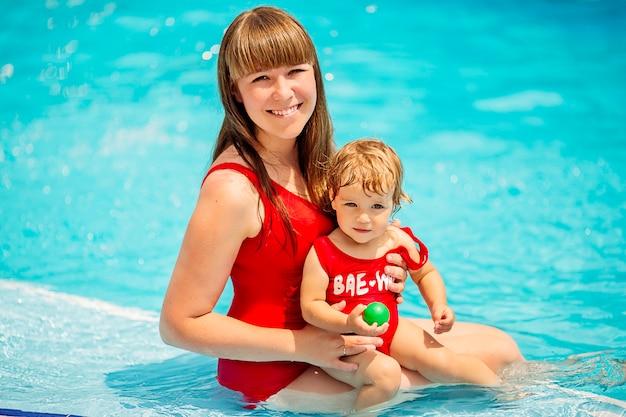 Прекрасная мама и дочка в красных купальниках улыбаются у бассейна