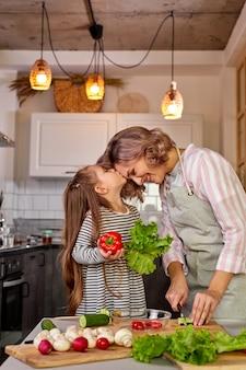 Прекрасная мать и дочь целуются на кухне во время готовки, готовя свежий салат из овощей
