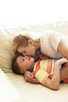 Милая мать и ее милый сын в объятиях дома