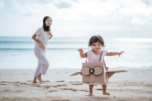 Lovely mother and daughter playing with airplane cardboard toy