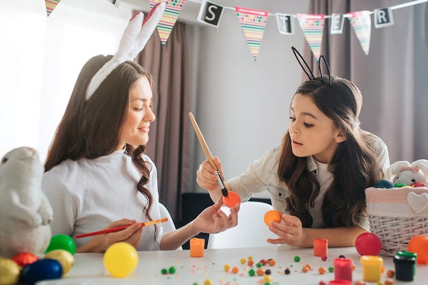 Lovely mother and daughter sit at table and paint eggs. they prepare for easter. girl hold paint brush. mother and child wear bunny ears.