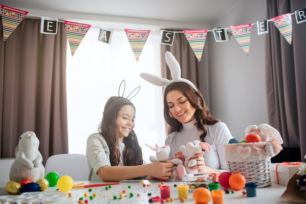 Lovely mother and girl prepare for easter. they play together with white bunny toys on table. family have fun together. decoration and paint on table.