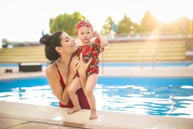Прекрасная мама обнимает ребенка в бассейне