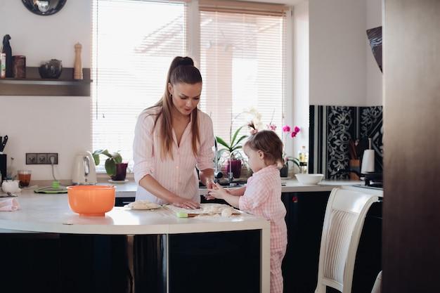 キッチンで小さな娘と遊ぶ素敵な母