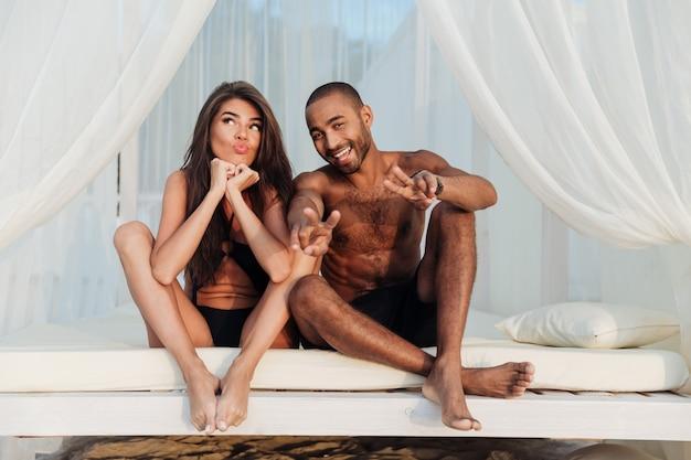 ビーチのベッドで楽しんでいる愛の素敵な多民族のカップル