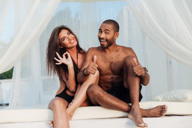ビーチのベッドで楽しんで、vサインと親指を表示して愛の素敵な多民族の笑顔のカップル