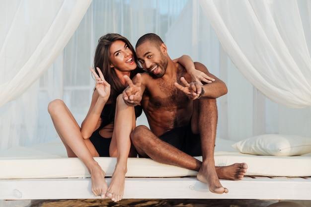 ビーチのベッドで楽しんで、vサインを示す愛の素敵な多民族の笑顔のカップル