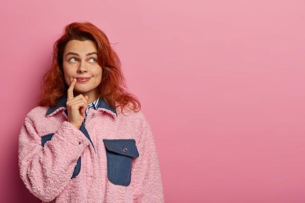 素敵な自然な赤毛の若い女性は、時間をうまく管理する方法を考え、何かを夢見ています