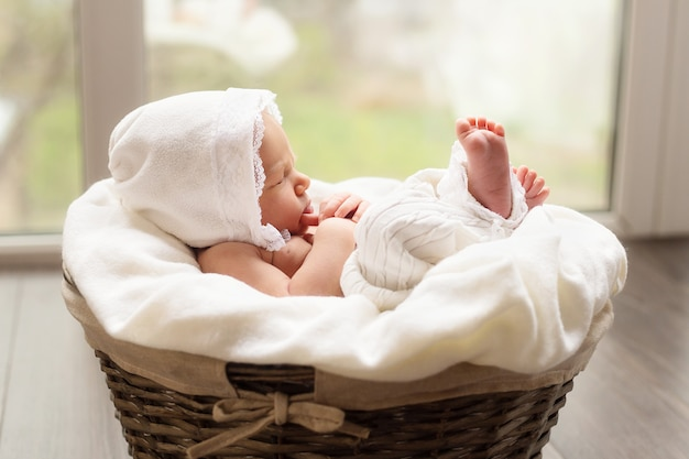 Lovely newborn baby girl is sleeping in the basket