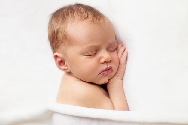 Lovely newborn baby girl is sleeping under the white blanket close up portrait