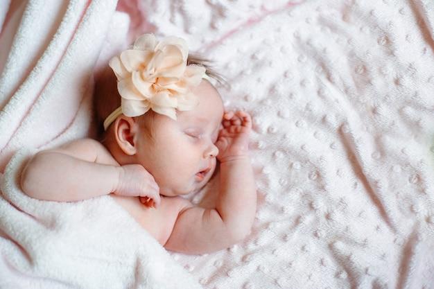 ピンクの毛布copyspaceで寝ている素敵な新生児の女の子