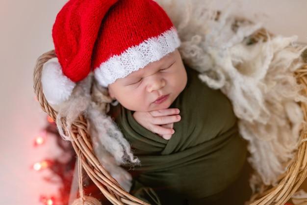 クリスマスの飾りにサンタの帽子をかぶっている素敵な新生児