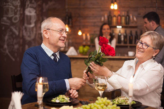 Lovely old lady admiring the flowers that her husband gave her. couple in their sixties having dinner. fresh grapes. glass of wine.