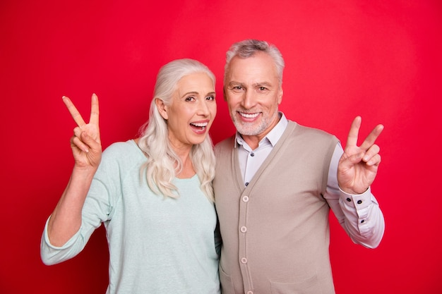 Lovely older couple posing against the red wall