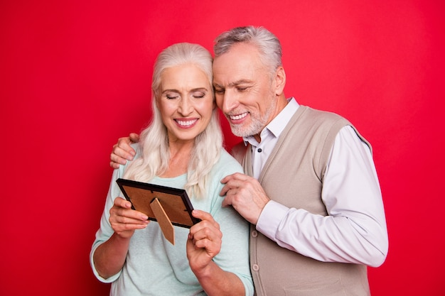 Lovely older couple posing together against the red wall
