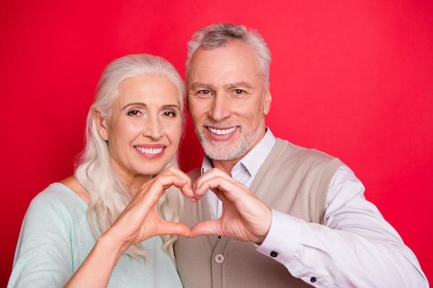 Прекрасная пожилая пара вместе позирует у красной стены