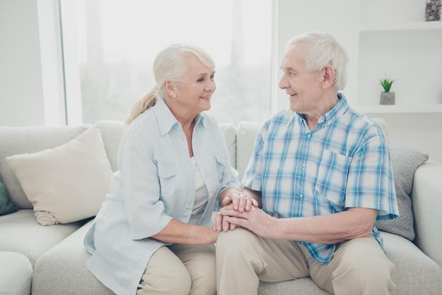 ソファで一緒にポーズをとる素敵な年配のカップル