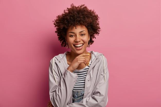 アフロの髪型を持つ素敵な楽観的な女性は、カジュアルなアノラックを着ています