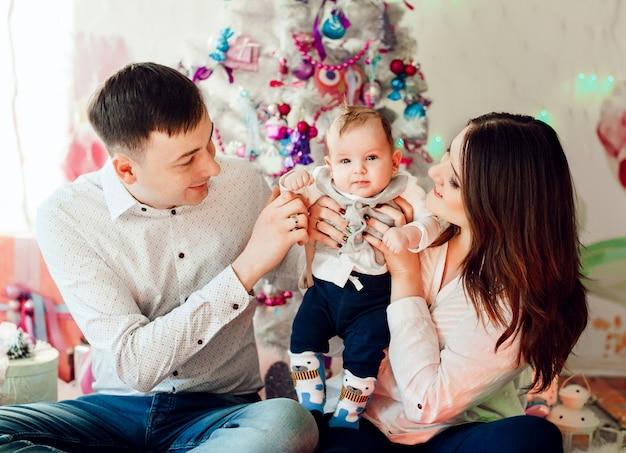 I genitori adorabili giocano con la piccola figlia prima di un albero di natale rosa