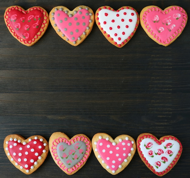 Lovely patterned heart shaped royal icing cookies on dark brown wooden background